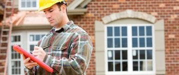 contractor making notes in front of new home