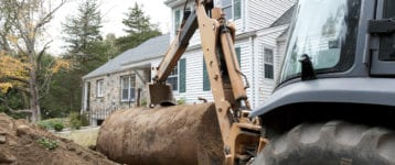 Old oil tank in front of house being removed