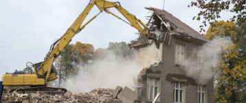 excavator demolishing a home
